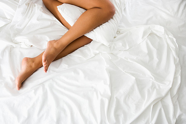 Woman lying in bed with pillow between legs