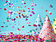 Colored confetti and party hat on blue background